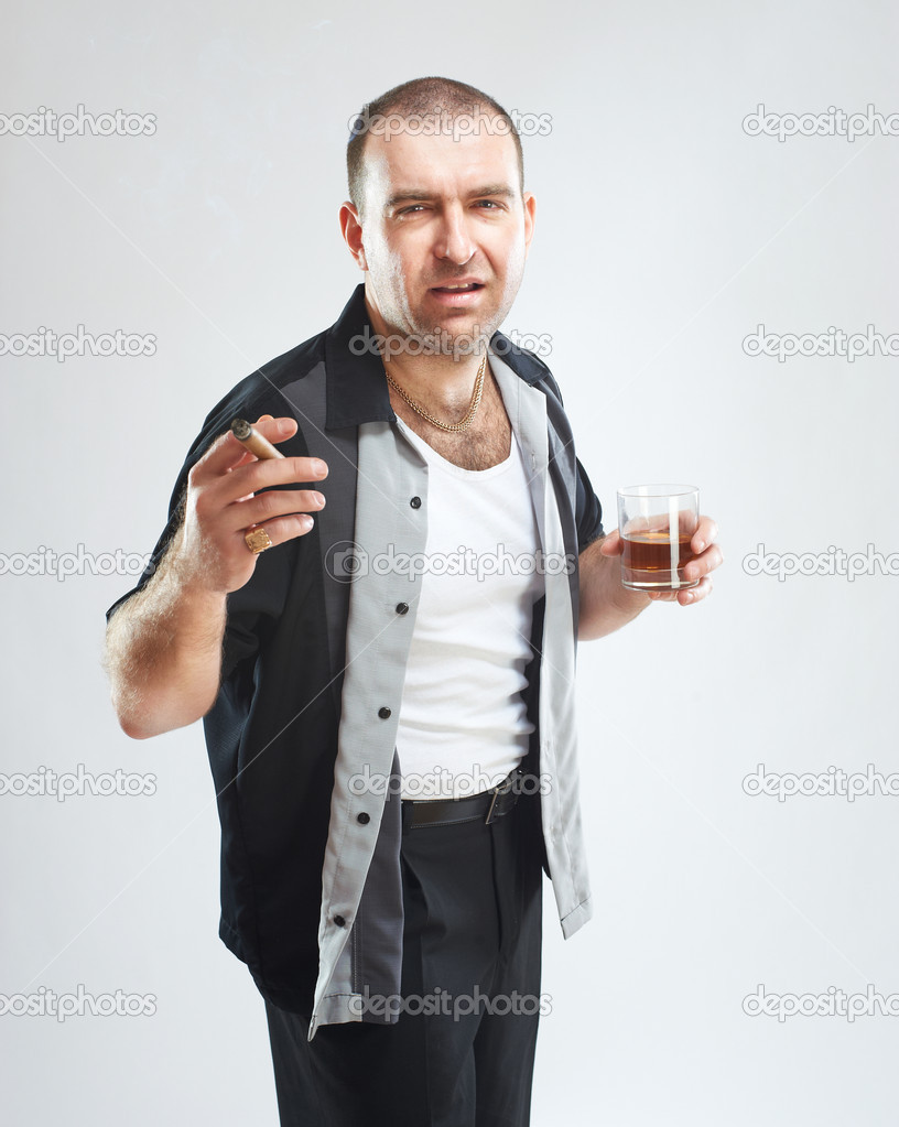 Portrait of serious tough guy with cigar and glass of alcohol