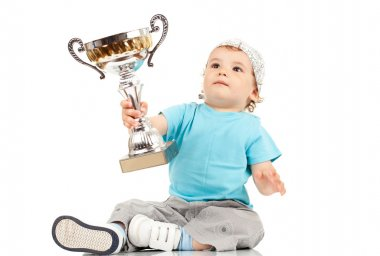 Small boy holding a winners cup