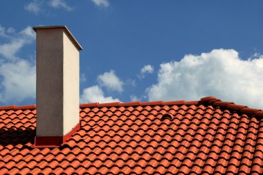 Red tiles roof and chimney with blue sky stock vector
