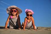 a homokos tengerparton fekvő két kislány