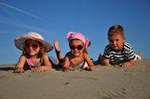 két kis lány és egy fiú a homokos tengerparton fekvő