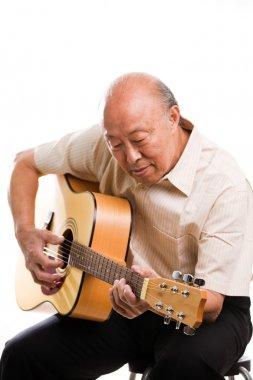 Senior asian playing guitar