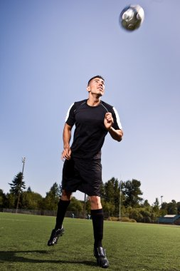 Hispanic soccer or football player heading a ball
