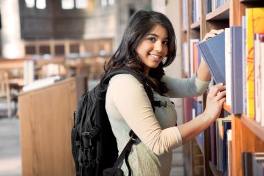 A shot of an asian student getting books in a library stock vector
