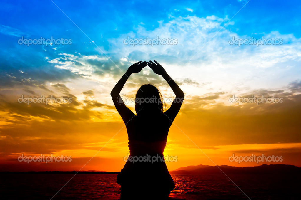 Silhouette of woman performs as yoga exercise on the beach during sunset