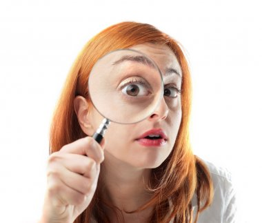 Young woman looking through a magnifying glass stock vector