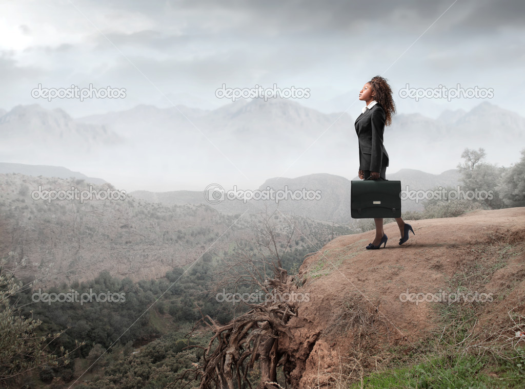 African businesswoman standing on a clearing over a highland