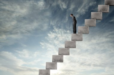 Businessman standing on a staircase and looking downwards stock vector