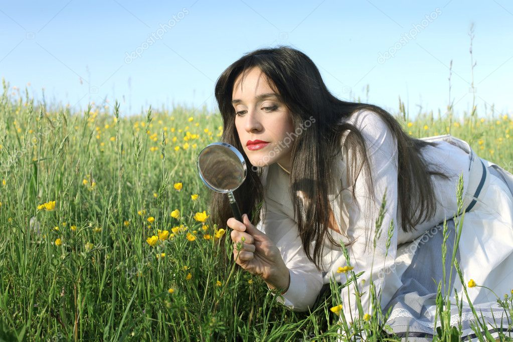 Young woman observing the plants of a meadow with a magnifying glass