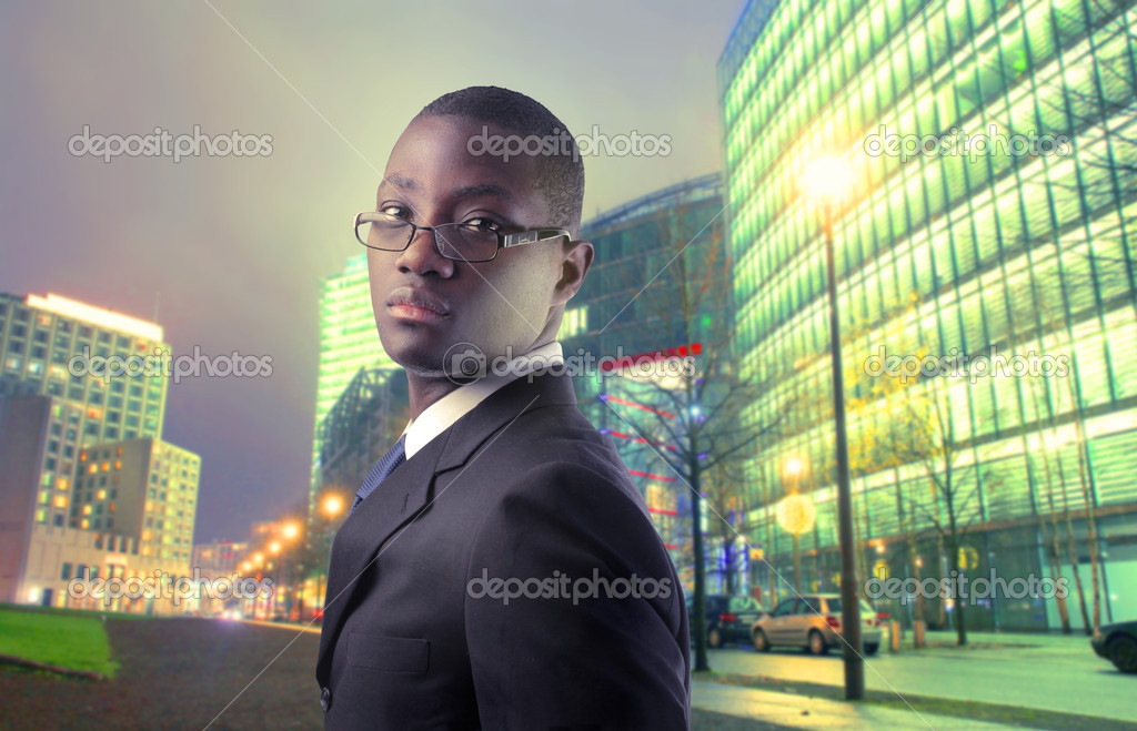 African businessman with city by night in the background