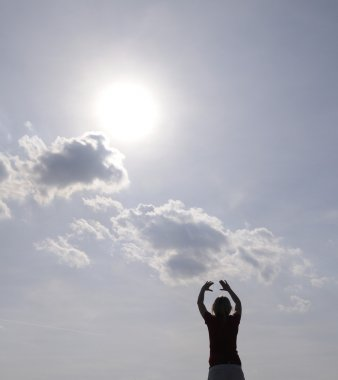 Woman stretched out her arms to the sun
