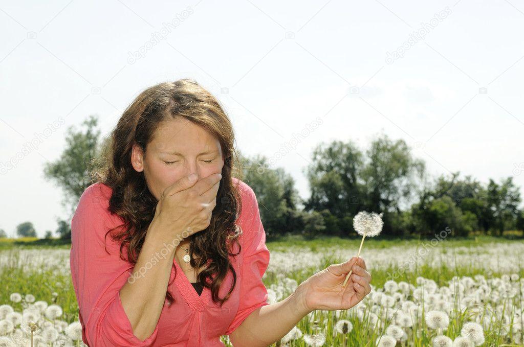 Woman sneezes on a flower meadow