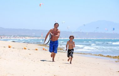 Young father and son running along beach with surfboard