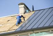 der Dachdecker hinter der Arbeit an der Reparatur des Daches
