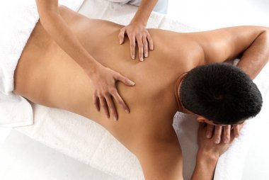 Unrecognizable man receiving massage relax treatment close-up from female h