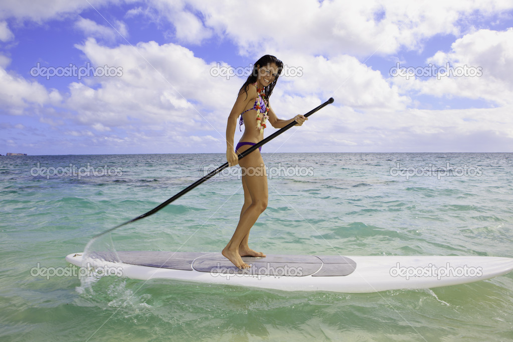 Brunette in bikini on her stand up paddle board