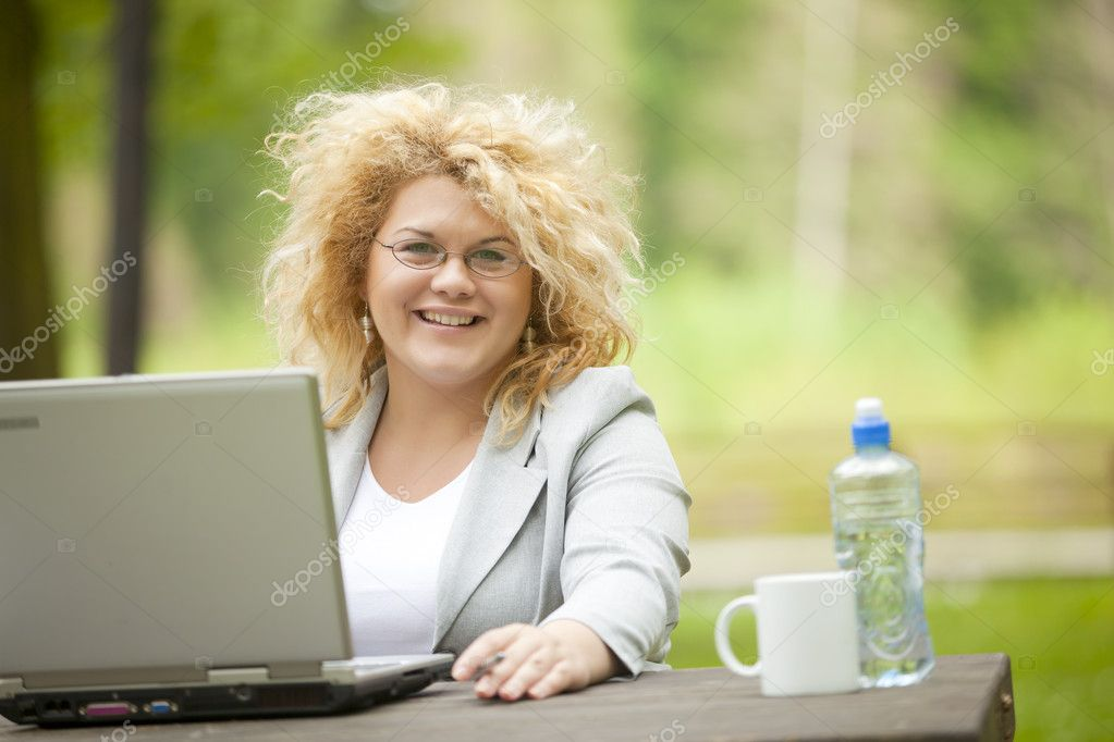 Happy Business Woman using laptop in park