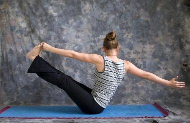 Woman doing Yoga posture Navasana variation or boat pose