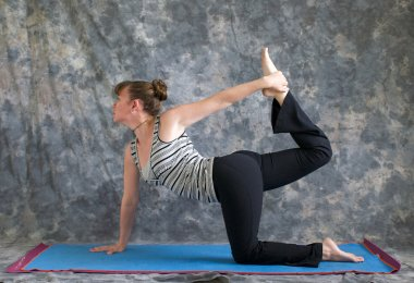 Woman doing Yoga posture Vyaghrasana The Tiger Pose variation