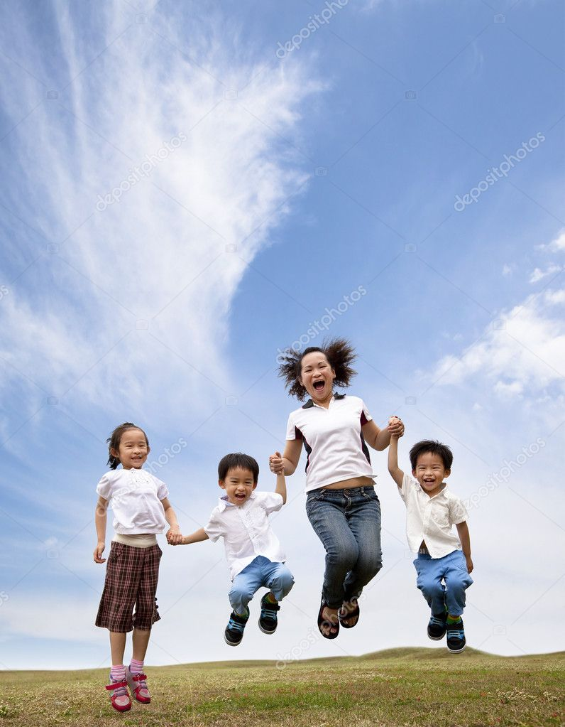 Happy asian family jumping on the grass field