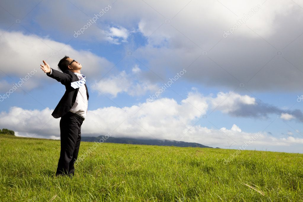 Young man in green field under blue skies