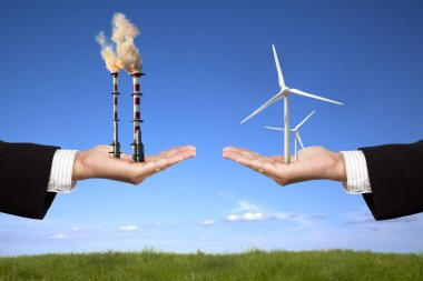 Pollution and clean energy concept. businessman holding windmills and refin