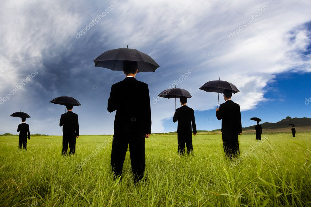Businessman in black suit holding umbrella