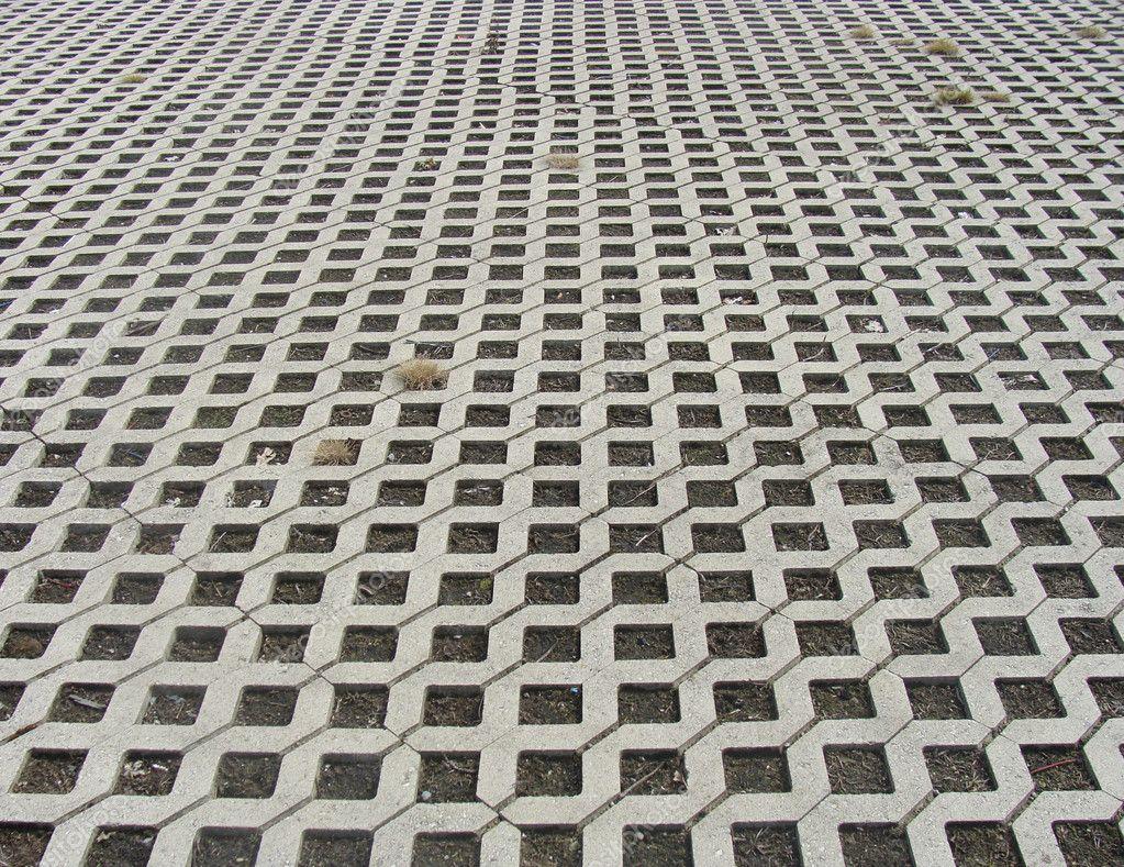 Quadrati forati pietra piastrelle pavimentazione con erba in mezzo