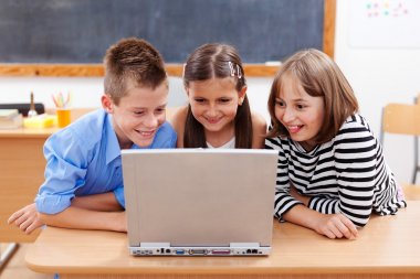 Happy kids looking at laptop