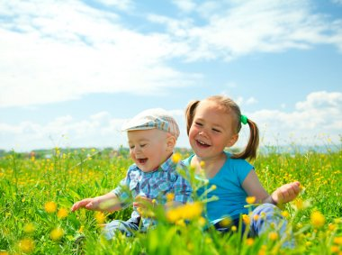Two children are having fun on green meadow