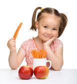 roztomilá holčička jí mrkev a jablka