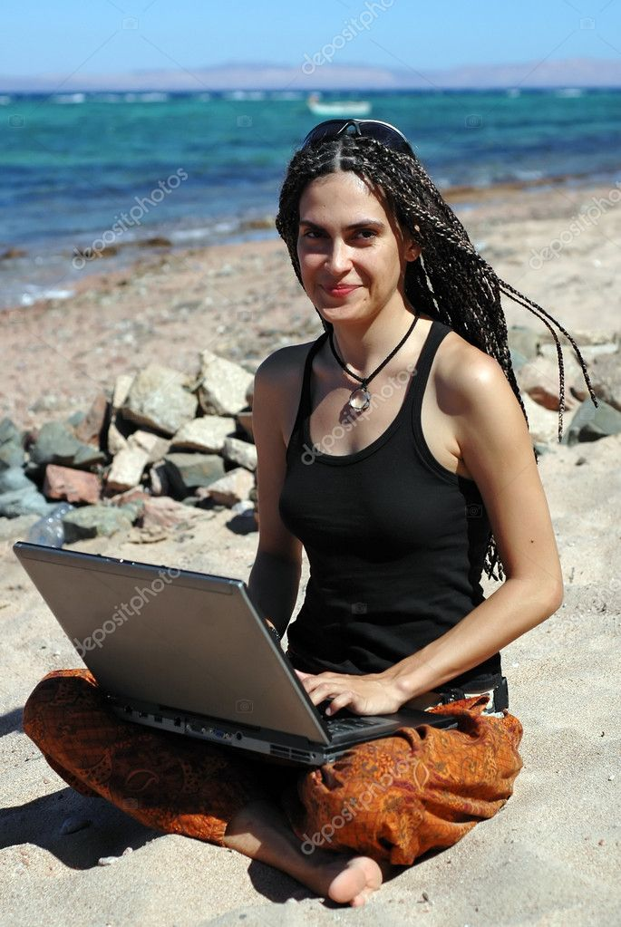 Girl with laptop on a beach