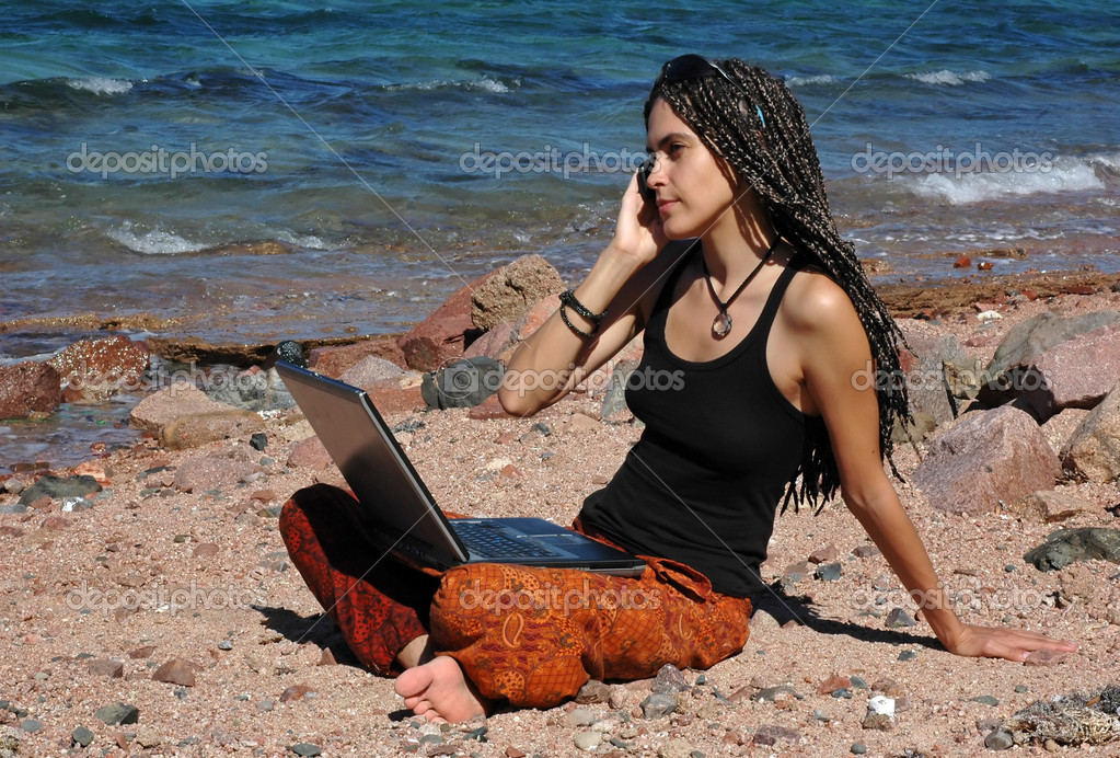 Girl with laptop and cellphone on a beach