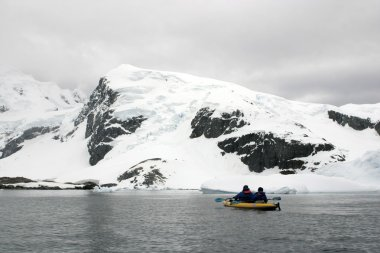 Kayaking in Antarctica, snow and cloudy weather
