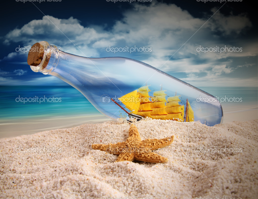 Ship in a bottle lying in the sand