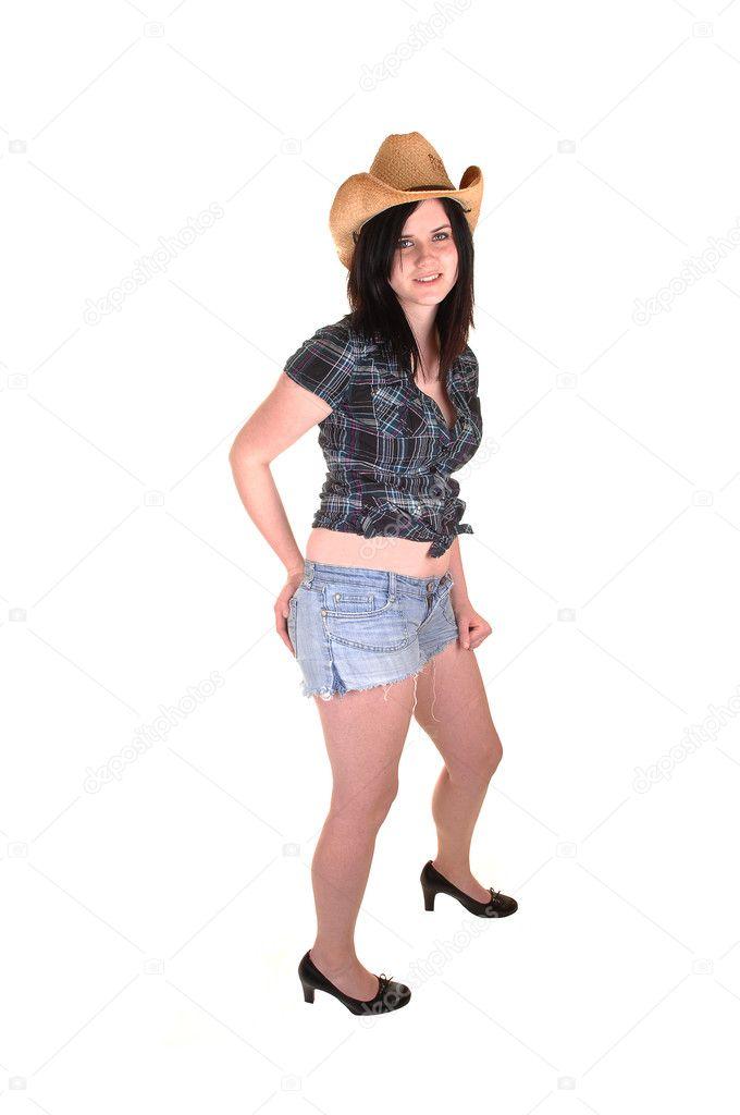 Una hermosa mujer joven en una blusa azul y sombrero vaquero parado en  shorts vaqueros en el estudio de fondo blanco — Foto de sucher 8ef529c7f89