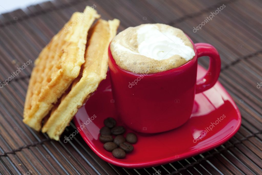 Cup of cappuccino wafers and coffee beans on a bamboo mat