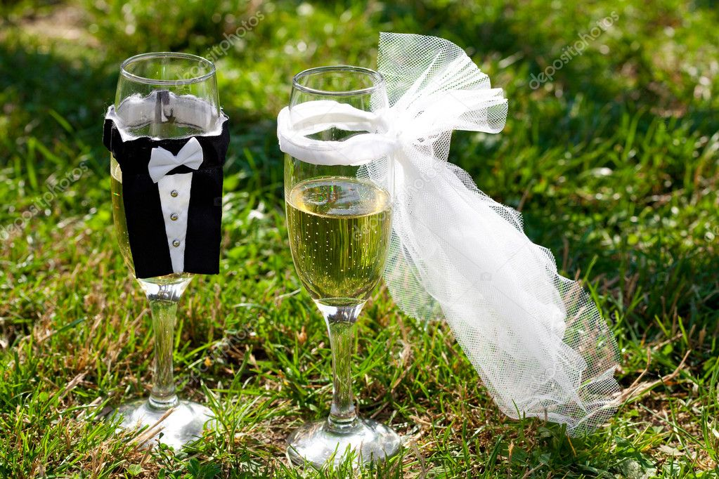 Two glasses of champagne in the clothes of bride and groom stand