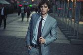 Fotografia bel ragazzo cammina su una strada di città di sera