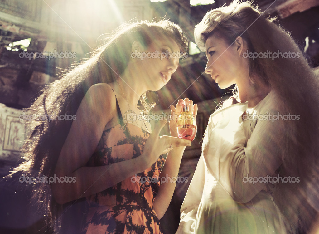 Two women holding magic flask