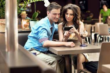 Cute woman showing something to her boyfriend on phone