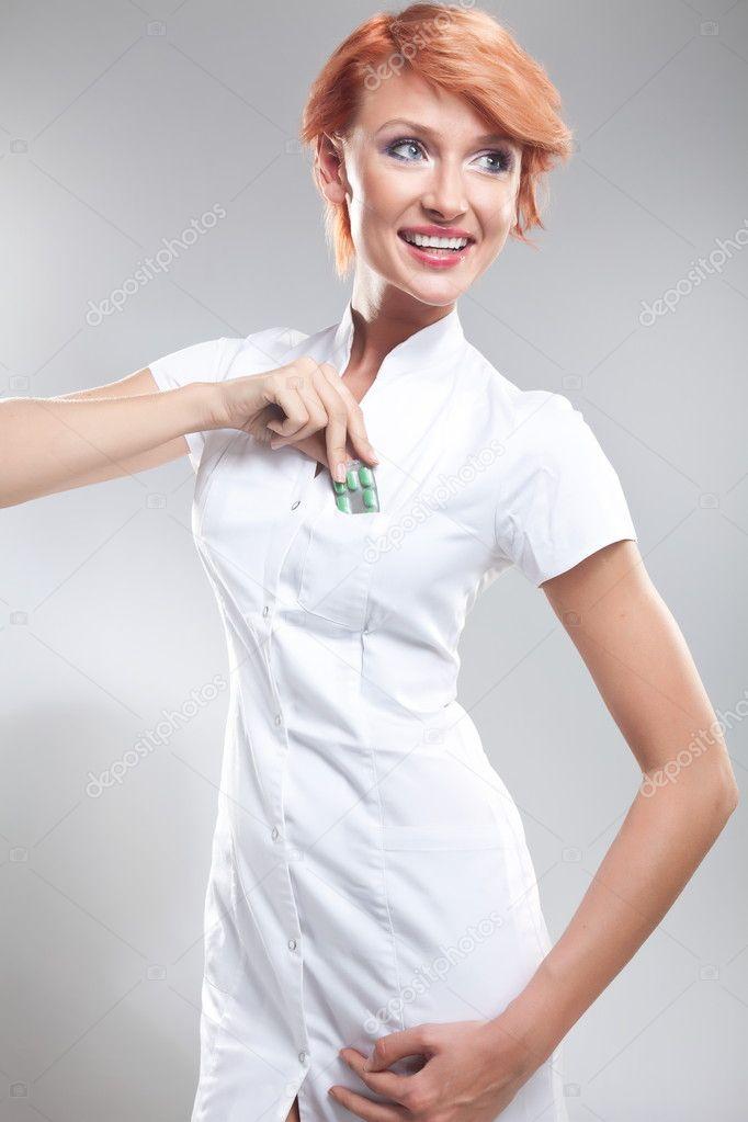 Smiling beautiful redhead woman showing pills
