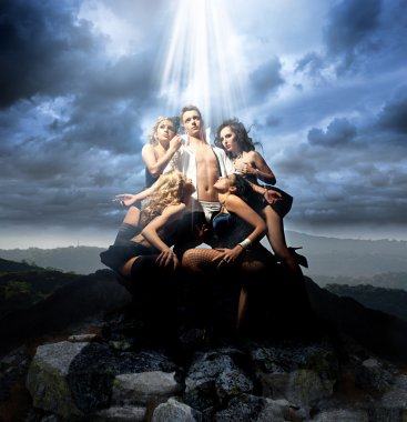 Sexy man surrounded by four attractive ladies on a mountain