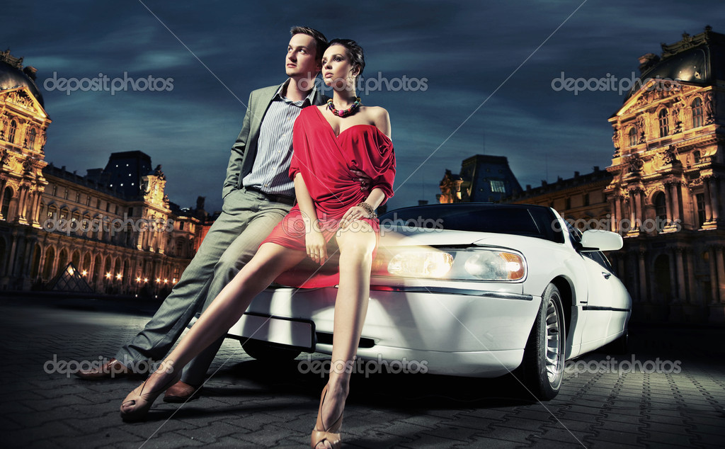 Sexy young couple in front of a limousine