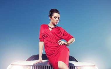 Elegant young lady in front of a white car