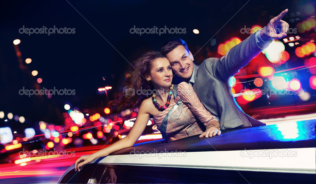 Elegant couple traveling a limousine at night