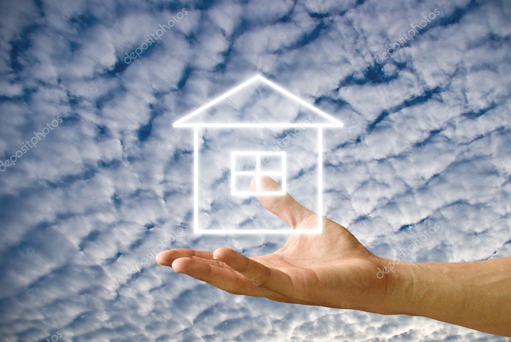 House icon in the hand with cloudy sky background