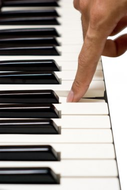 Artist finger on piano key