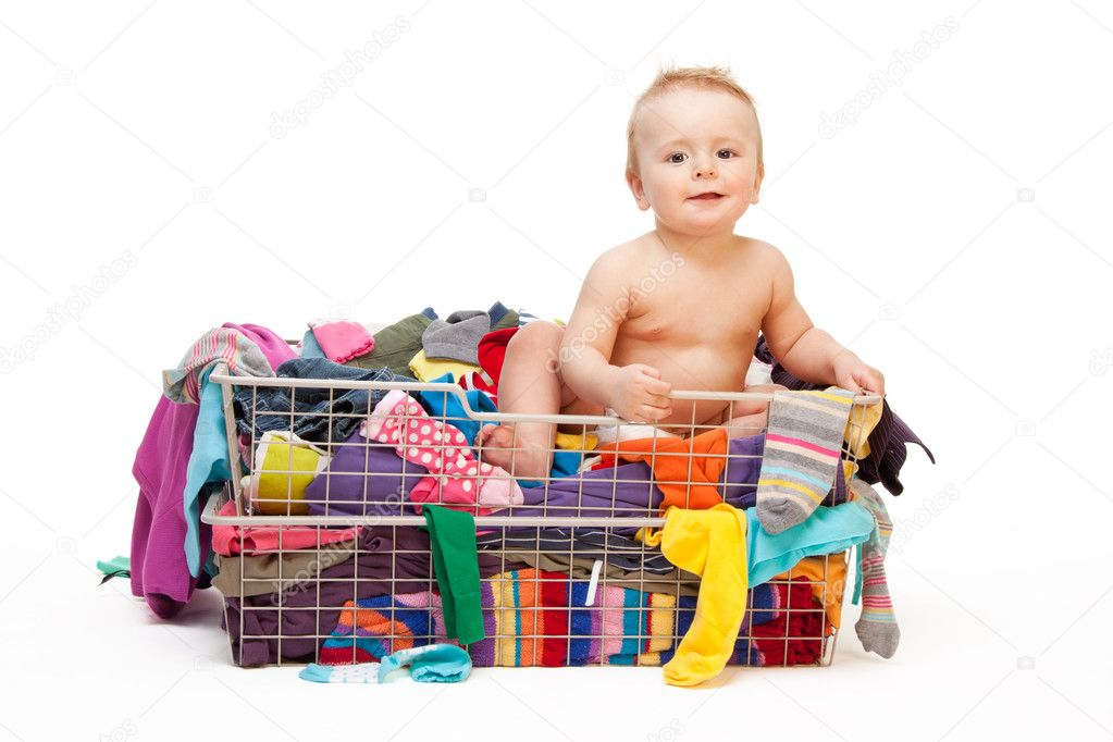 Happy baby in basket with clothes isolated on white
