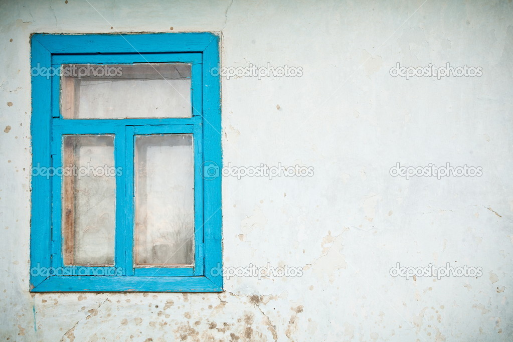 Old cracked wall with window painted with blue